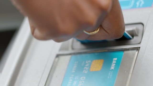 female hand inserting a bank card into an atm - inserting stock videos & royalty-free footage