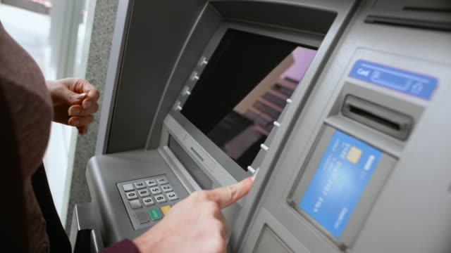 LD Female hand inserting a bank card into the ATM slot, entering PIN number and choosing from the display menu