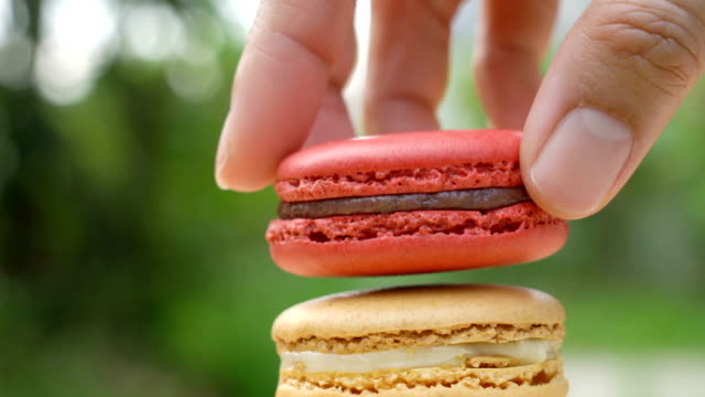 female hand picking macaron out of frame. - macaroon stock videos & royalty-free footage