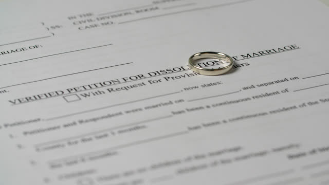 female hand places ring on divorce paper - dissolving stock videos & royalty-free footage