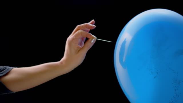vidéos et rushes de slo mo ld main femelle popping un ballon rempli de confettis avec une broche - gestes