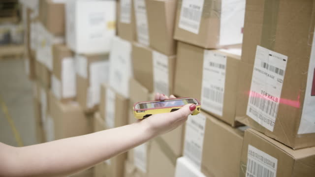 female hand scanning packages with a small handheld barcode scanner - distribution warehouse stock videos & royalty-free footage