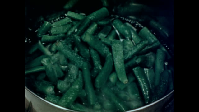 Female hand tears open frozen vegetable box / shakes contents into a pot of water / green beans cooking in the pot Cooking frozen green beans on...