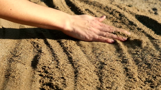 Female hand touching sand