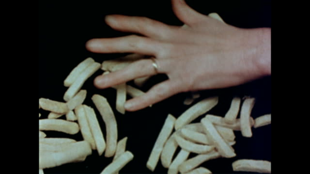 female hand with wedding ring sprinkles the contents of a frozen food box onto a black surface / frozen french fries are spread out frozen french... - 1954 stock videos and b-roll footage