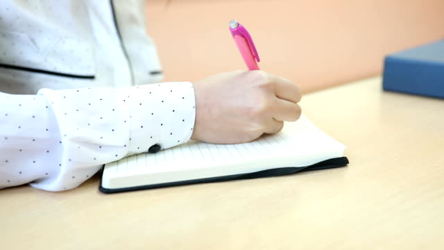 female hand writes a note in a notebook - diary stock videos & royalty-free footage