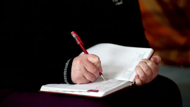 female hand writes a pen in a diary