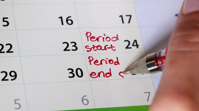 female hand writing a period reminder in calendar using a red pen - diary stock videos & royalty-free footage