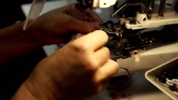 Female hands, a young tailor sews buttons with sewing machine on a silk blouse. Sewing Button machine. Close up