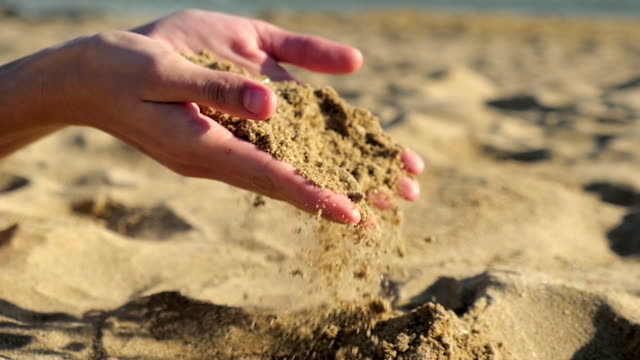 Female hands and falling sand