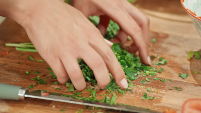 vídeos de stock e filmes b-roll de female hands chopping fresh herbs on a wooden board and putting it on a salad - comida e bebida
