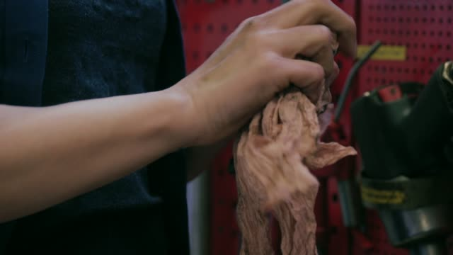 Female hands cleaning mechanic tools with a rag