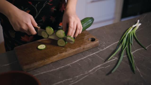 female hands cuting cucumber on wooden board in kitchen - sich verschönern stock-videos und b-roll-filmmaterial