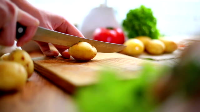 Female hands cutting potatoes on wooden board.