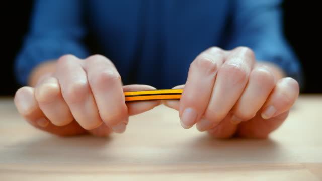 vidéos et rushes de slo mo ld mains femelles retenant un crayon et le cassant - irréductibilité