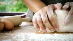 Female hands kneading dough in flour with green tree blurred background