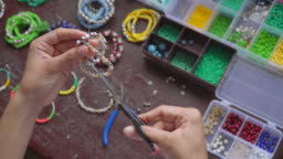 Female hands making handmade jewelry with little balls and stones