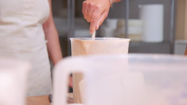 vídeos de stock, filmes e b-roll de mãos femininas misturando mistura de cerâmica em um frasco - praticando