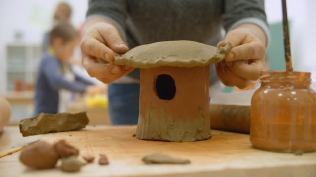 female hands placing a roof on top of a bird house made of clay - birdhouse stock videos & royalty-free footage
