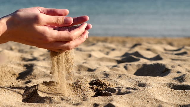 Female hands playing with sand