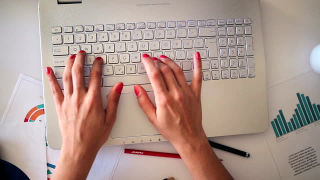Female hands typing laptop computer keyboard, top view