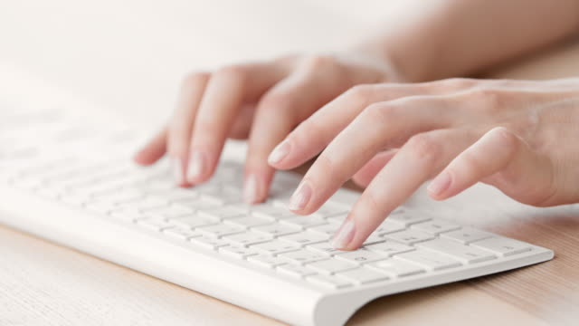 female hands typing on a white keyboard - typing stock videos & royalty-free footage