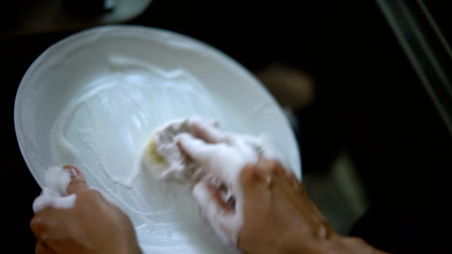 4k female hands washing dishes with flowing water. - lavastoviglie video stock e b–roll