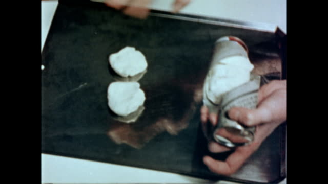 female hands wearing wedding ring opening a biscuit dough tube / hand places individual biscuits on a tray. preparing biscuit dough on january 01,... - オーブンの天板点の映像素材/bロール