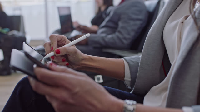 Female hands with red nail polish use tablet and stylus while diverse buisness travelers work in background.