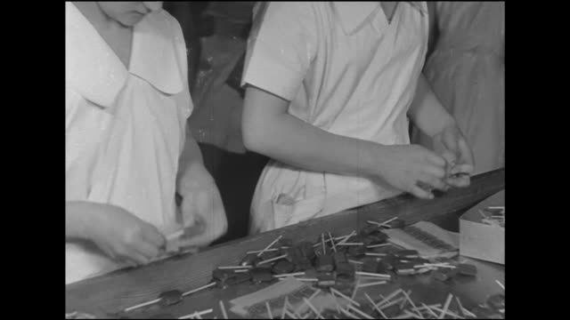 female hands wrapping suckers in paper wrap. woman placing lollipop suckers onto conveyor leading into wrapping machine, female hand sorting... - lollipop stock videos & royalty-free footage