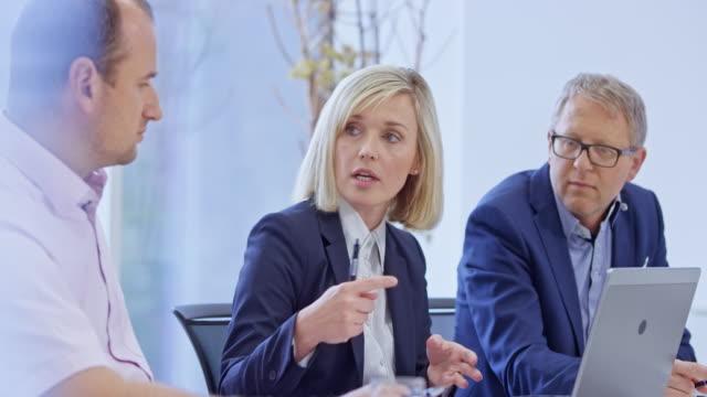 weibliche leiterin der finanzabteilung im gespräch mit dem führenden ingenieur im besprechungsraum - drei personen stock-videos und b-roll-filmmaterial