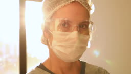 Female health care worker portrait with sun on background
