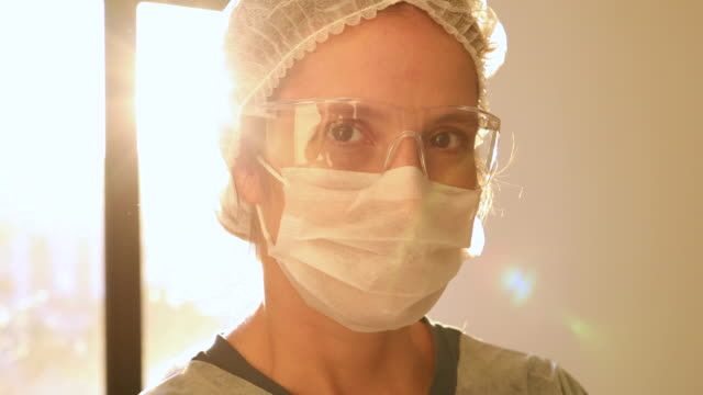 female health care worker portrait with sun on background - surgeon stock videos & royalty-free footage