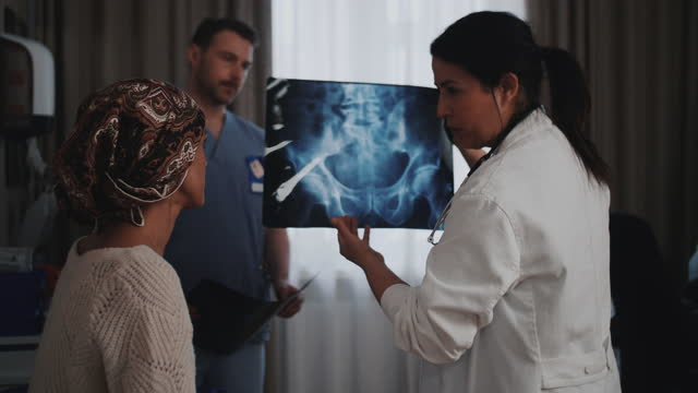 female healthcare expert showing pelvis x-ray image to patient suffering from cancer at clinic - 骨盤点の映像素材/bロール