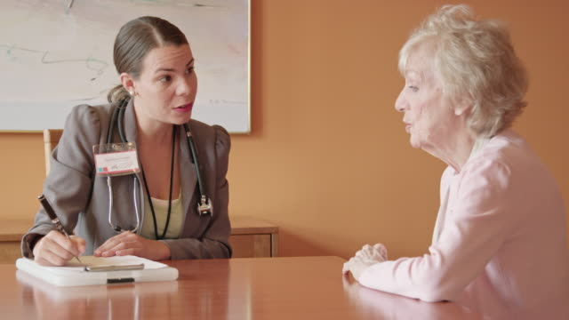 female healthcare professional asks questions of senior woman - social services stock videos & royalty-free footage