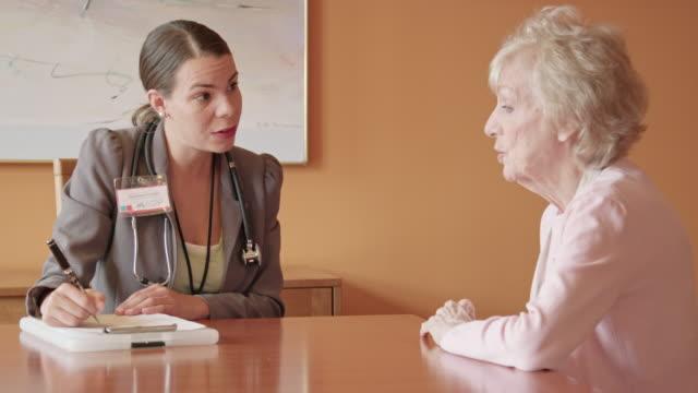 female healthcare professional asks questions of senior woman - servizio sociale video stock e b–roll