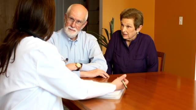 Vrouwelijke gezondheidszorg professionele gesprekken met Senior paar