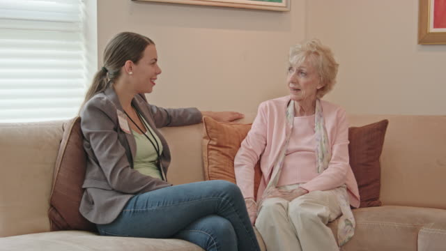 female healthcare professional talks with senior woman - the ageing process stock videos & royalty-free footage
