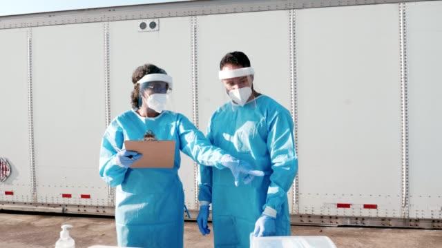 stockvideo's en b-roll-footage met vrouwelijke zorgverlener leidt nieuwe medewerker op bij covid-19 testlocatie - medicijnflesje