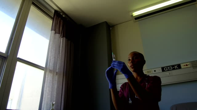 female healthcare worker preparing a sharp for injection - latex glove stock videos & royalty-free footage