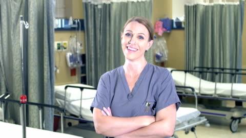 vídeos y material grabado en eventos de stock de trabajadora de la salud femenina de pie en la sala del hospital - one mature woman only