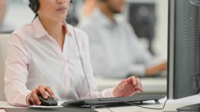tu weibliche helpline operator einen anruf entgegennimmst, - callcenter stock-videos und b-roll-filmmaterial
