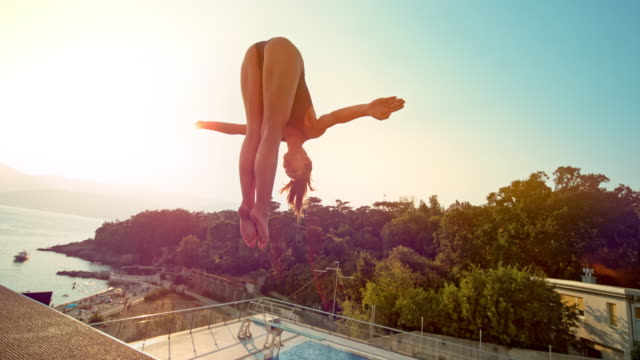 slo mo female high diver taking off the platform at sunset - 20 24 years stock videos & royalty-free footage