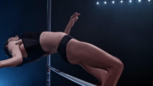 vídeos de stock, filmes e b-roll de slo mo female high jumper clearing the bar - atleta de campo e pista