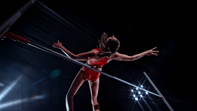 slo mo female high jumper jumping over the bar on black background with stadium reflector lights - sport video stock e b–roll