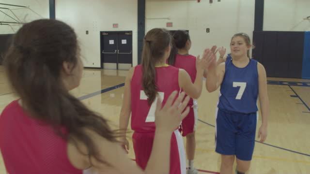 Weibliche High-School-Basketball-Spieler Händeschütteln und andere Team gratuliert
