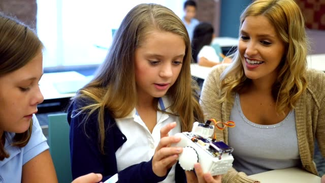 Female high school STEM students examine a robot in technology class