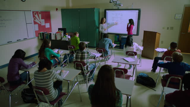 a female high school student completes an equation on a smart board during class. - interactive whiteboard stock videos & royalty-free footage