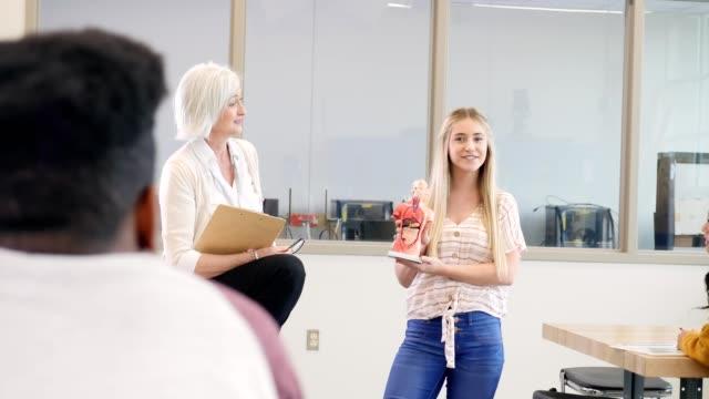 vidéos et rushes de étudiant féminin de lycée donne une présentation pendant la classe de biologie - élève