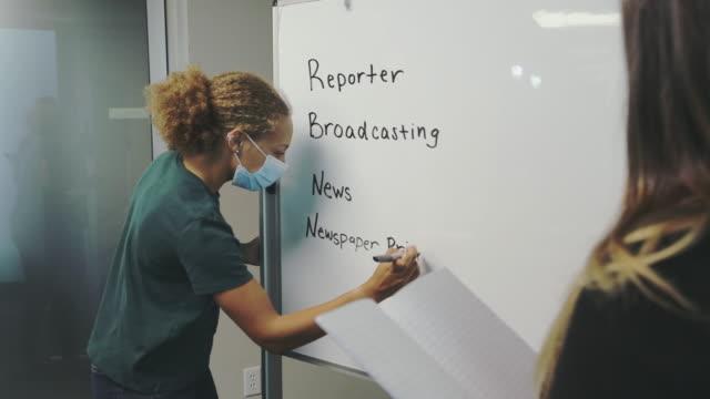 weibliche high school student schreiben auf whiteboard in klassenzimmer einstellung tragen maske 4k video - western script stock-videos und b-roll-filmmaterial